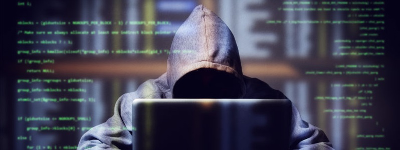 Hooded Hacker Behind Laptop